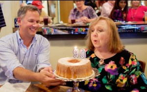 CANDLE IN THE WIND--With North Carolina Lieut. Governor Dan Forest looking on, Betty extinguishes the 90 candles on her birthday cake. Photo by Hobart Jones.