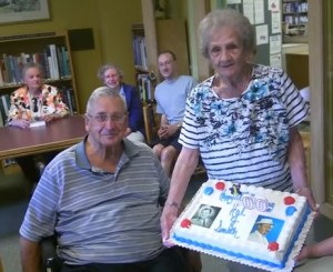 HAL TO CELEBRATE--The late Hal Smith's first cousins David MacMillan and Theodora Rose display a custom cake as others look on during the party marking Hal's 100th birthday. Photo by John D. Michaud III.