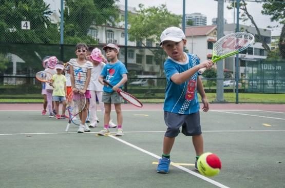 Junior Tennis Camp, little boy hitting a tennis ball by TAG International Tennis Academy