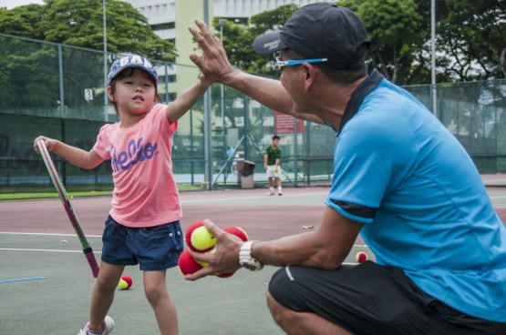 Junior Tennis Camp with kids high-five with coach by TAG International Tennis Academy