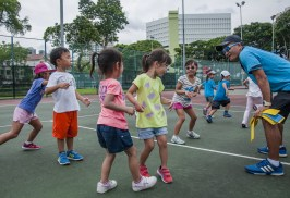 Junior Tennis Camp with coach talking to the kids by TAG International Tennis Academy