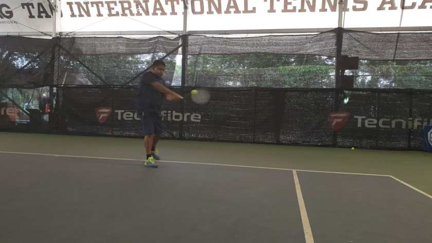 Coach Ten Rapeepat has a square contact with the ball as he hits the forehand early on the rise