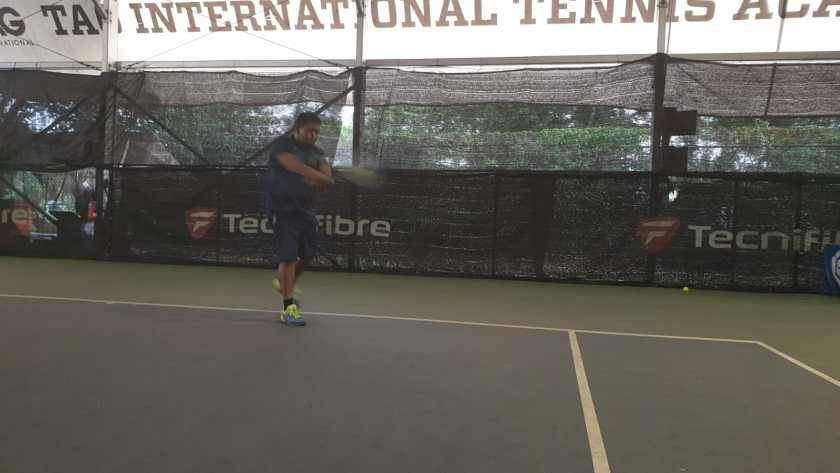 Coach Ten Rapeepat hits the forehand early on the rise