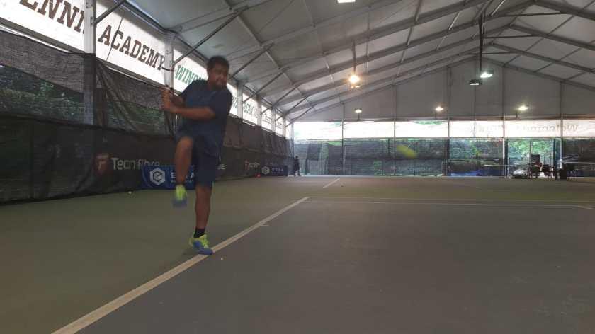Coach Rapeepat Thonghatt prepares to hit a high backhand