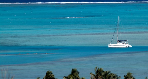 Tahina at anchor in Aitutaki in channel between sand and reefs