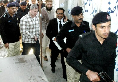 Pakistani security officials escort a U.S. consulate employee, who has not been named by US authorities, second from left, at a local court in Lahore, Pakistan on Friday, Jan. 28, 2011. Pakistan will pursue murder charges against the employee suspected of shooting two armed men during a possible robbery attempt, a top prosecutor said. (AP Photo/Hamza Ahmed)