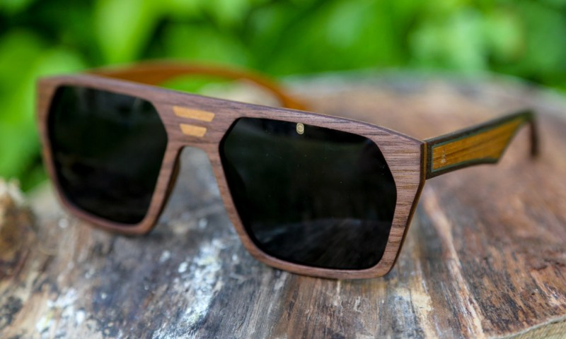 Wooden sunglasses (the Skylands) sit on a wooden base. In the background of the image is green foliage.