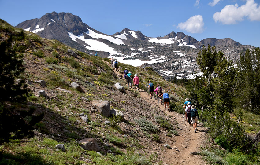 Group of colorfully dressed hikers en route to Winnemucca Lake