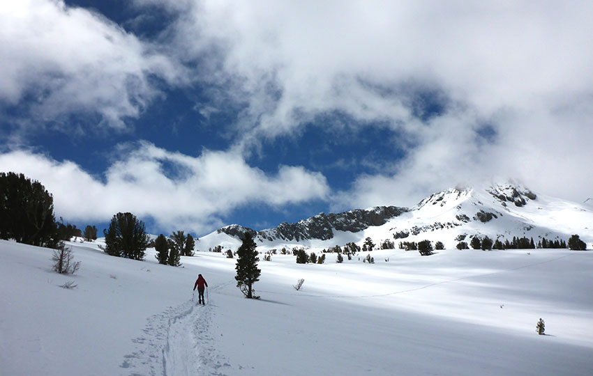 Cross-country skiing on tracks that lead to a snowy mountain with dramatic clouds overhead