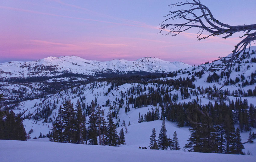 Pastel-colored skies at dusk over a snowy mountain range