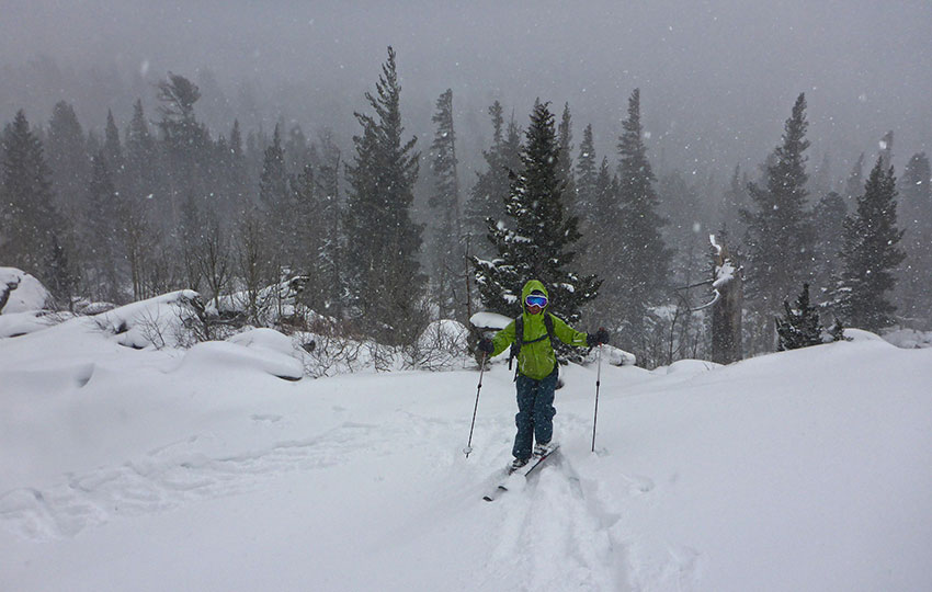 Snowstorm with a cross-country skier climbing a hill