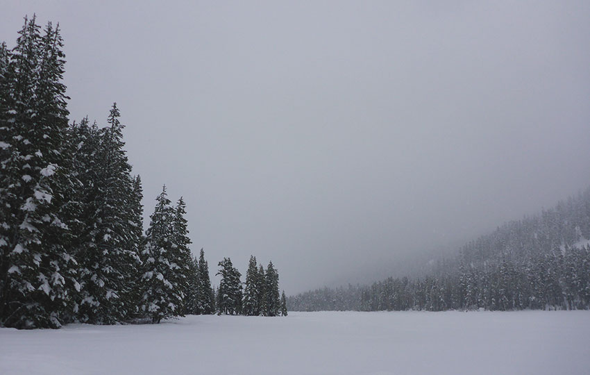 Overcast skies and as snow-covered lake flanked by forests
