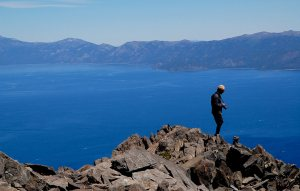 Man with camera and brimmed hat on mountain summit overlooking Lake Tahoe