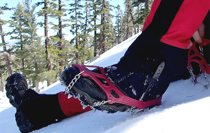 Putting on foot traction devices in snowy terrain