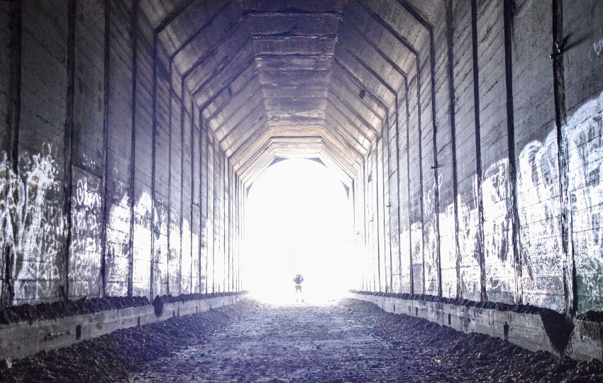 Hiker bathed in light while walking out of a dark tunnel