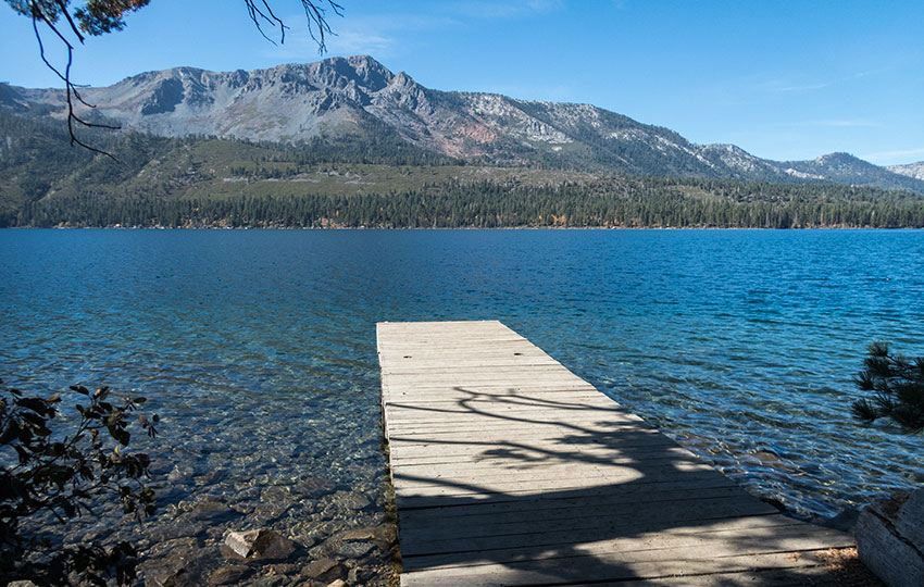 Dock at an alpine lake with mountains in the background