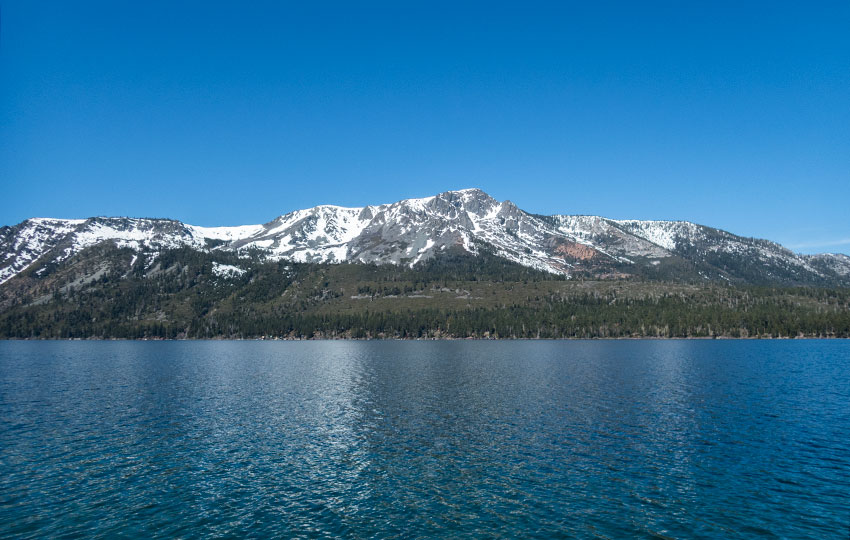 Snow covered mountains behind an alpine lake