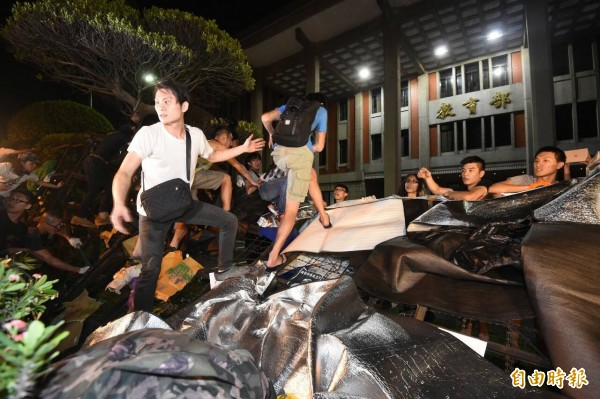 students climbing over the collapsed barrier to enter the square in front of the MOE