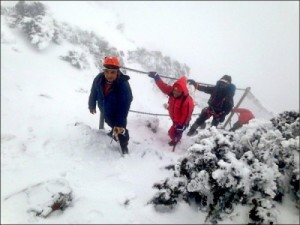 A search and rescue team climbing a steep slope in snow on Mount Jade in Taiwan