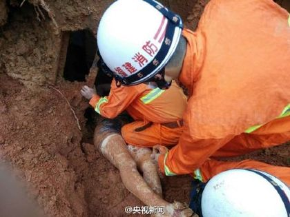rescue workers dig a woman out of a landslide