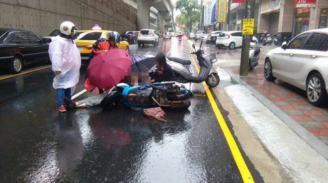 bystanders hold umbrellas over an injured pedestian after she was hit by a scooter