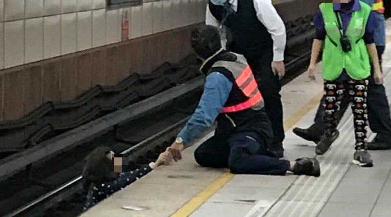 woman helped back onto platform after falling onto tracks while using phone