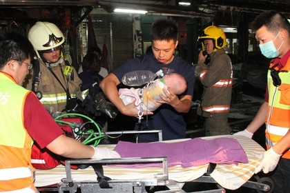 a baby is treated by paramedics at the scene of a fire