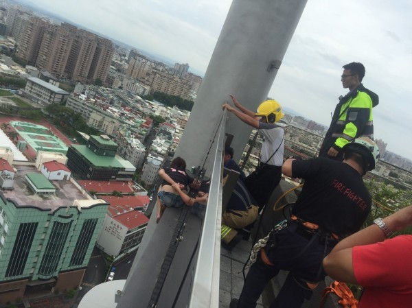 woman on roof ledge of high-rise building police and firefighters