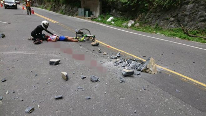 cyclist on road after being injured by falling rocks