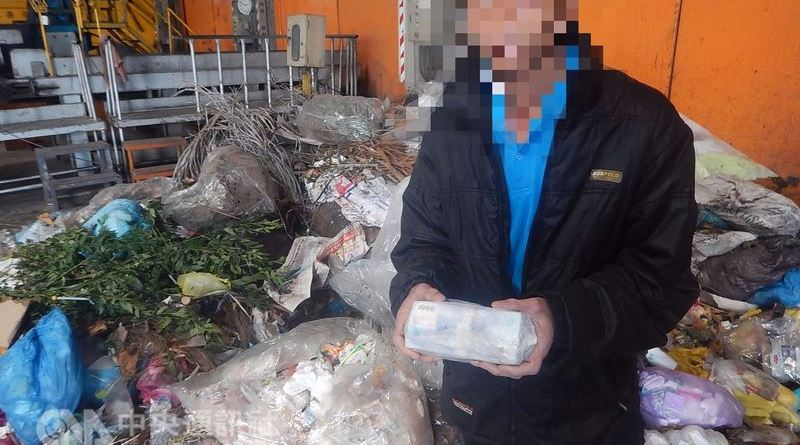 a man holds a bundle of cash recovered after throwing it out with the trash