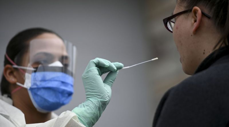 medical worker about to swab inside somebody's mouth