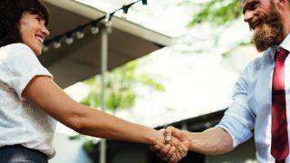成功を分かち合って握手する二人