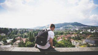 コンクリートの上に座るバックパックを背負った若い男性