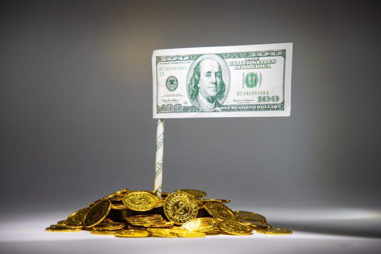 貨幣の上にたつ100$紙幣