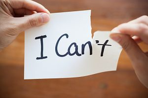 Hands Tearing Paper with Words - I Can't become Can