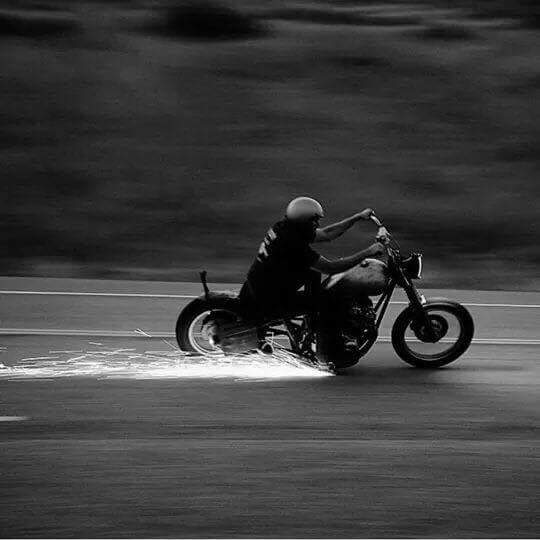 A black and white photo of a retro harley davidson kicking up sparks while racing around a bend in an empty back road