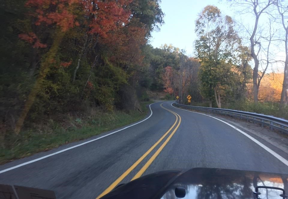 A twisty back road is lined with color as the initial leaf change of fall starts to occur.