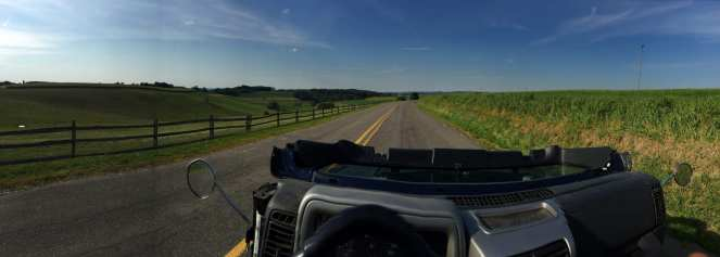 A Jeep Wrangler on back roads with the top off and windshield down