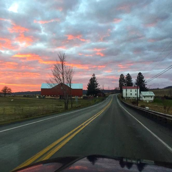 A beautiful sunset erupts over a back road cutting through farm country. A big red barn and old farmhouse line the road. Learn how to find back roads like this one using a map.