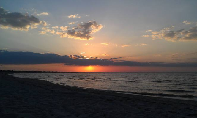 A beautiful pink and orange beach sunset rewards the back roads reader for finishing the blog!