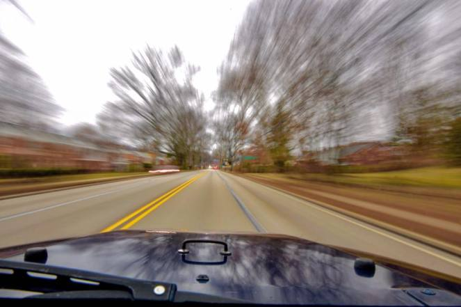 Trees and houses blur around a blue Jeep hood from the speed of back roads travel