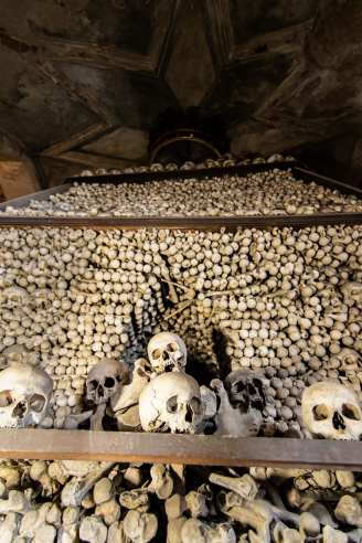 massive pyramid of human bones with skulls in the foreground