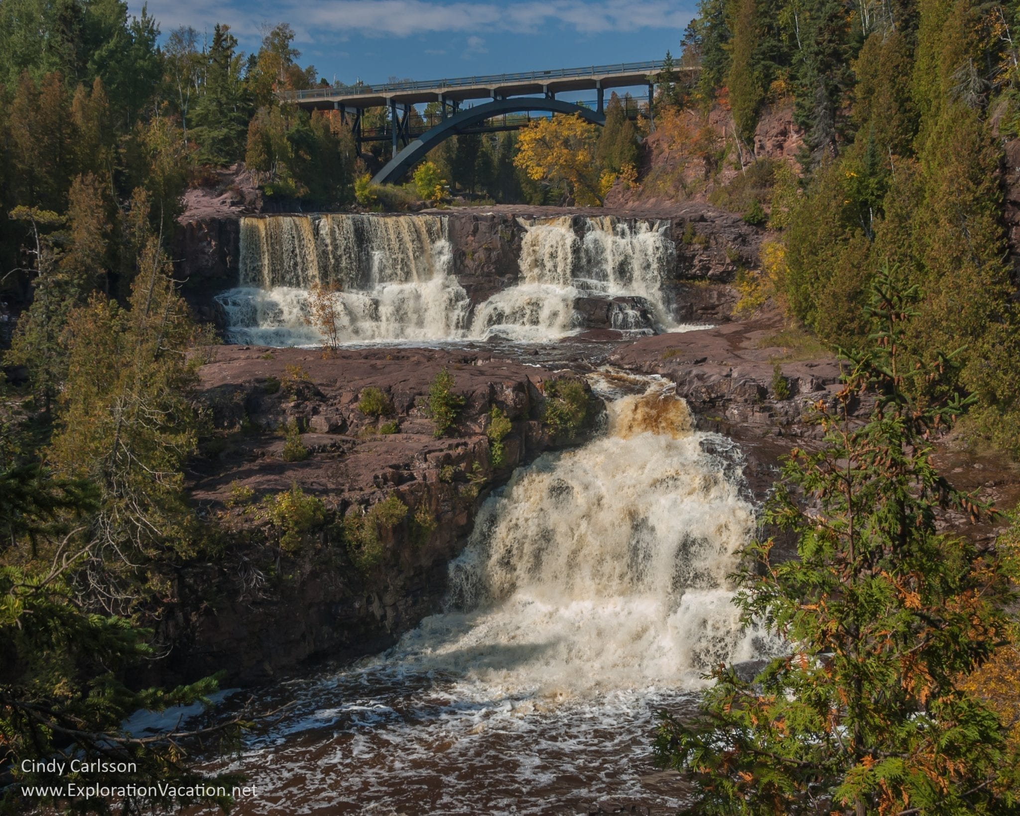 gooseberry falls bridal veil waterfall rushing water arch bridge evergreen forest