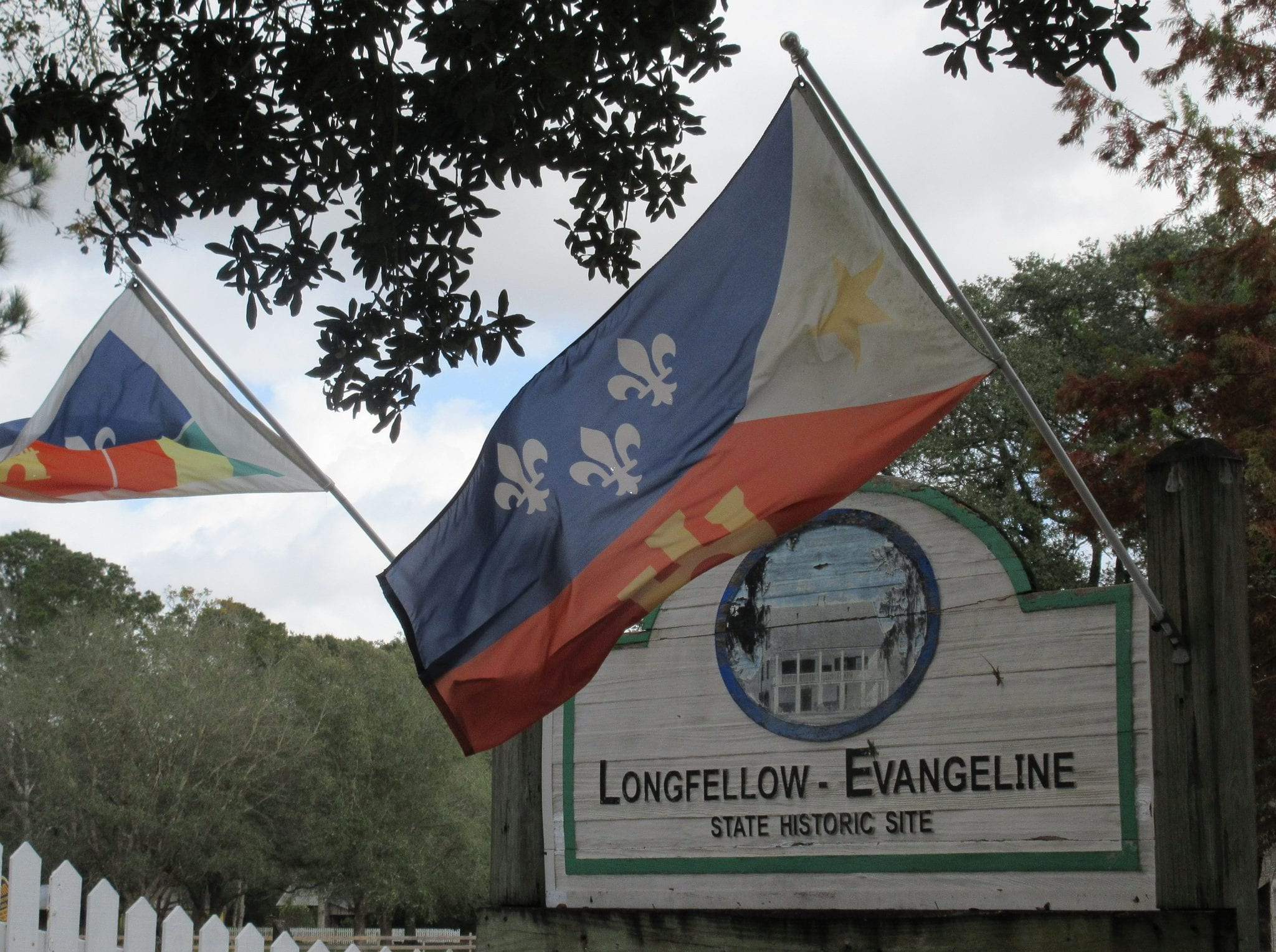 longfellow evangeline historic site welcome sign flags magnolia tree