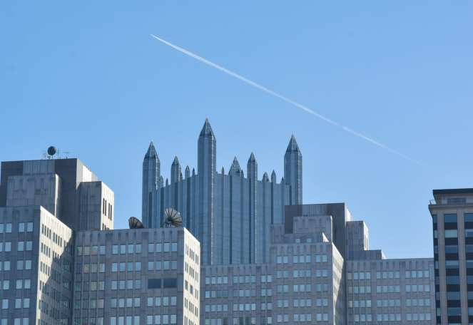 The Gateway Center Buildings create a cube-like foreground, framing the iconic spires of the PPG Building in downtown Pittsburgh while a single airplane creates a long contrail overhead