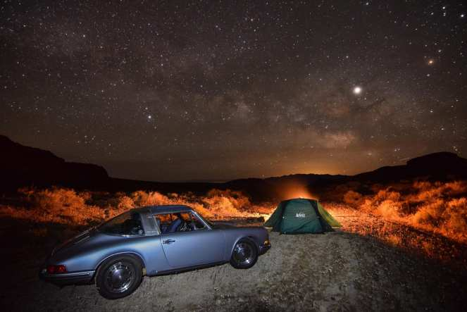 The Milky Way stretches over a fire lit campground, tent, and an antique Porsche 911
