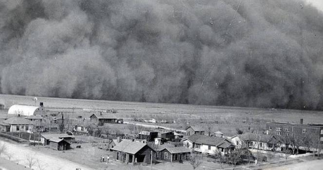 A large cloud of dust bears down on a small farming village in this black and white photo