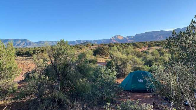 A green REI tent is tucked into the shrubbery of Coconino National Forest outside of Sedona Arizona, providing us with comfort and shelter during our cheap cross country road trip.