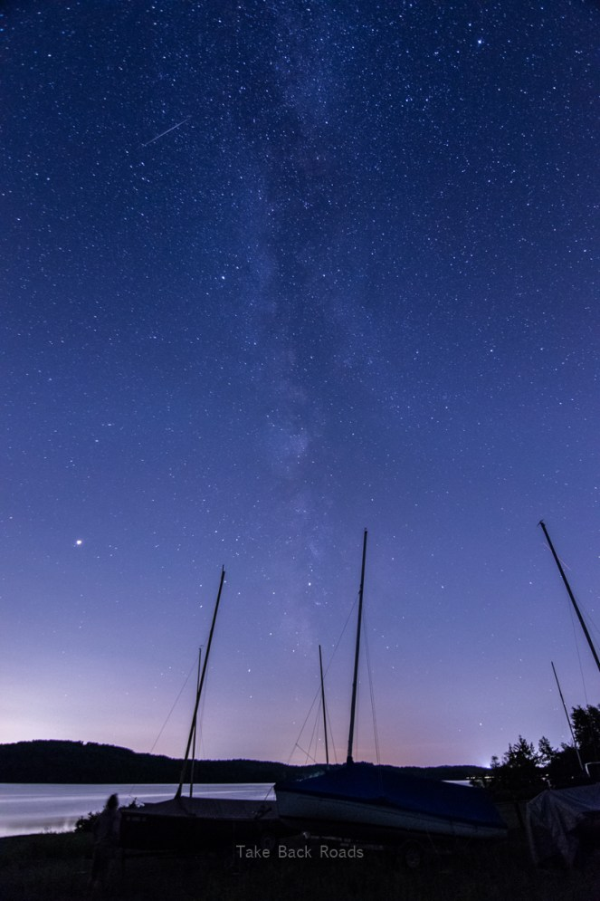 A shadowy marina and the masts of several boats frame the Milky Way and starry night sky overhead. A small glimpse of a nearby lake is visible.