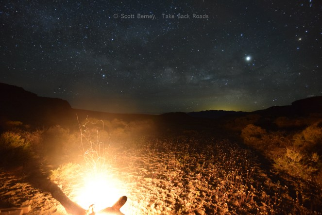 Night sky over campfire. Milky Way and campfire. Our campfire lights up the desert floor while the Milky Way spans the dark night sky overhead.